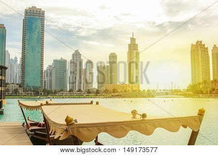 The tour boat used by tourists to see the show of the Dubai Fountain, docked near the Souk Al Bahar in the Burj Khalifa Lake. On background, the tall skyscrapers at sunset in Dubai Mall area. poster