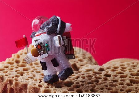 Spaceman explores red planet Mars. Light bulb character dressed in spacesuit and astronaut ammunition. Cosmonaut with flag walking abstract planet landscape. creative astronomic concept.