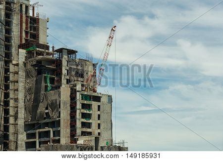 Building and cranes under construction against blue sky.