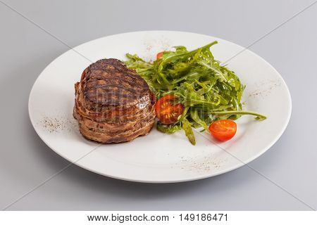 Grilled bbq steak wrapped bacon, green salad with cherry tomatoes on white plate, gray background. horizontal photo