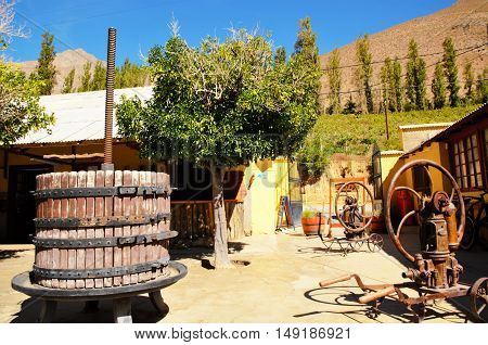 Long shot of a traditional manual Pisco factory with a barrel and different machines in Pisco Elqui, Chile, South America poster