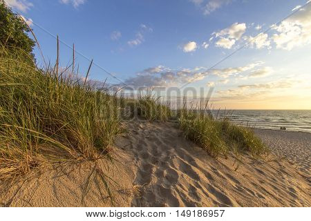 Warm Summer Breeze. Sunny afternoon day at the beach with a sand dune in the foreground and the beginnings of a sunset at the water's horizon. Hoffmaster State Park, Michigan.