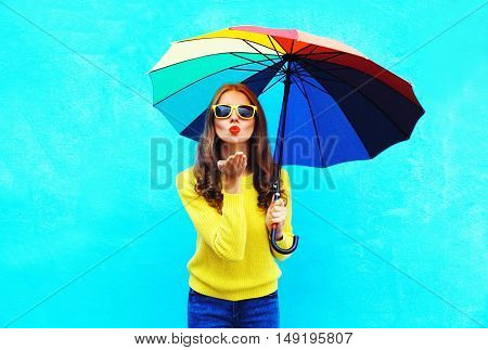 Pretty Young Woman With Colorful Umbrella Sends Air Sweet Kiss In Autumn Day Over Blue Background We
