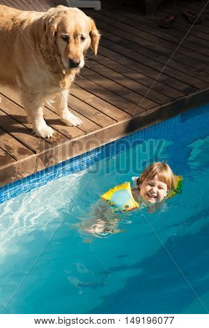 Laughing Child In Water Pool And Dog