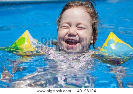 three years old blonde child with yellow floater sleeves in arms laughing face swimming in blue water of swimming pool poster