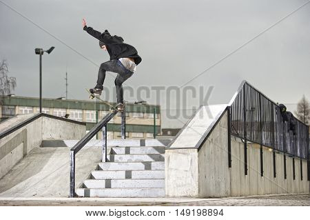 Boy doing skateboard bluntslide trick on rail