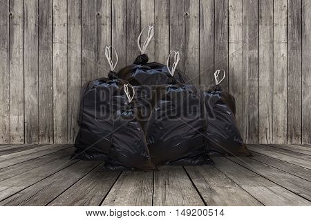 Pile of full black garbage bags with wooden background