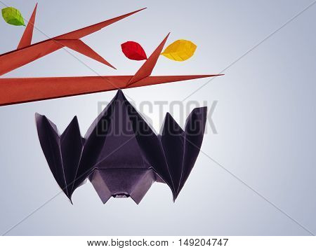 Origami paper halloween hanging bat on a branch on blue background