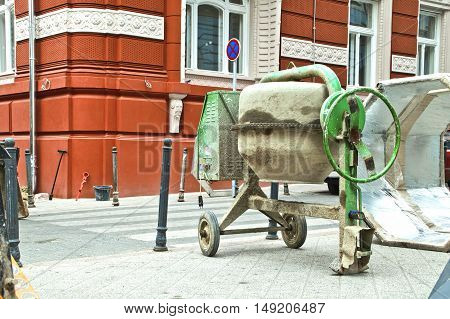 Green cement mixer on building site work area