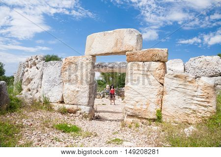 woman tourist visiting prehistoric monument in ancient town from Talayotic times in X century Before Christ in Torralba den Gaumes or Galmes in Alaior Menorca Balearic Islands Spain Europe