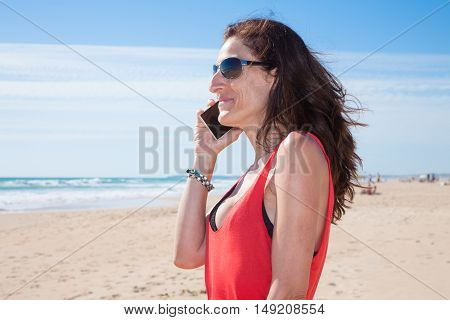 Woman With Sunglasses Talking On Phone At Beach