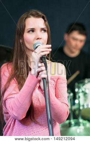 Female singer in pink dress near microphone. Attractive woman standing on scene and ready to talk. Master of ceremonies, mc, soloist