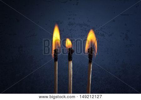 Matchsticks with flame over a dark grunge background