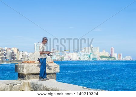 HAVANA CUBA - JULY 18 : Cuban fisherman at the seafront wall of the Malecon in Havana on July 18 2016. The historic center of Havana is UNESCO World Heritage Site since 1982.