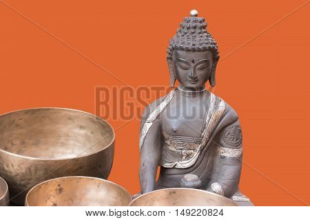 Old bronze sculpture (statue) of Buddha on orange background with bronze bowls in front of the figure