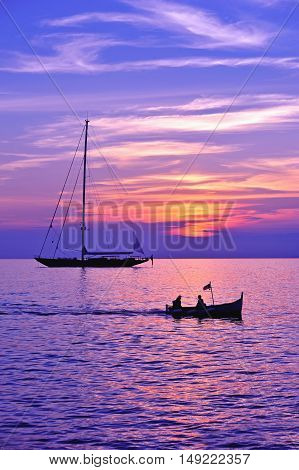 purple sky under sea with boat and sailing ship silhouette
