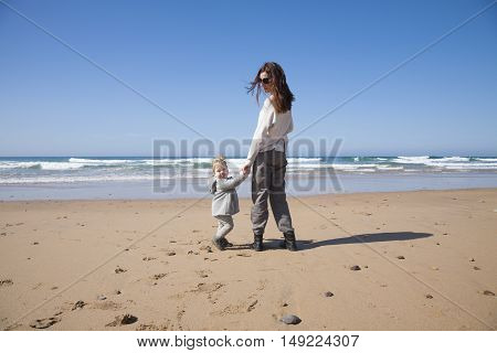 two years age blonde baby with grey coat and brunette mother woman holding hands looking backwards camera in sand of beach in front of water sea or ocean