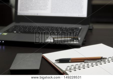 A desk full of work equipment such as the book with pen external HDD computer notebook and credit card