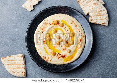 Hummus, chickpea dip, with spices and pita, flat bread in a black plate on grey stone background Top view