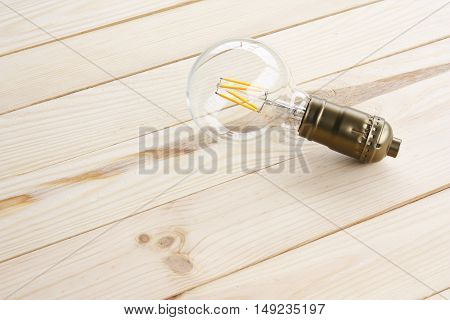 Lamp light bulb on top view wood table with space for business idea and vision solution. new vintage light bulb concept of new ideas innovation invention and creativity.