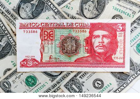 Three Cuban Pesos Bill With Coin Three Pesos Over Several Dollar Bills