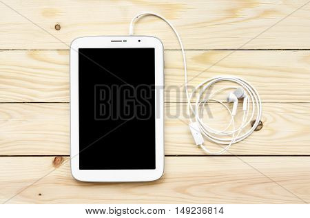 white tablet with earbuds top view wood table included clipping path for tablet display