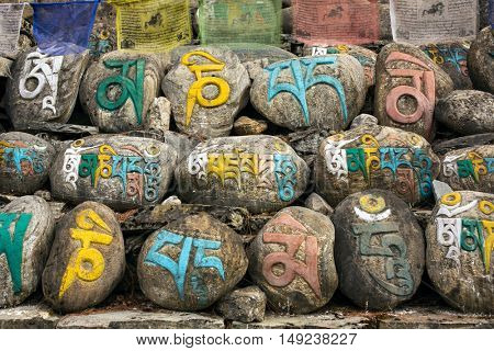 Malang, Nepal - May 4, 2016: Mani stones in Nepalese village, ancient buddhist carved stones with sacred religious mantras written in Tibetan language