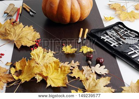 Still life with pumpkin, carving tools and autumn decorations