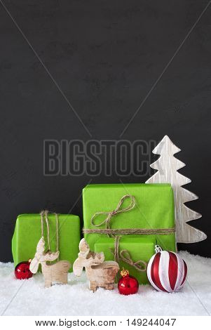 Green Gifts Or Presents With Christmas Decoration Like Tree, Moose Or Red Christmas Tree Ball. Black Cement Wall As Background With Snow. Vertical Christmas Greeting Card