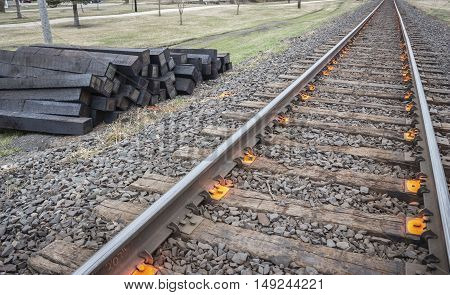 horizontal image of railroad ties lying beside the tracks ready to be changed.