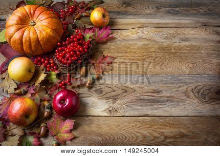 Thanksgiving greeting background with pumpkins apples and fall leaves. Thanksgiving background with seasonal vegetables and fruits.