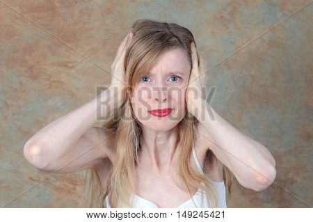 Young woman holding her ears to protect them from loud noise