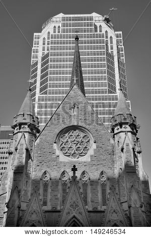 MONTREAL CANADA 09 16 2016: Montreal Anglican Christ Church Cathedral in front the Tour KPMG or Place de la Cathedrale, is a 34 storey skyscraper located in Montreal that was completed in 1987