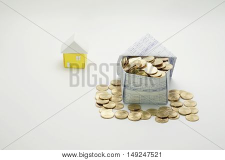 House of gold coins and little house on white background.