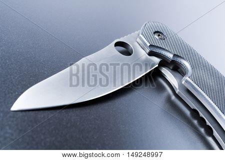 Macro Of A Lying Half Opened Faint Military Knife On Dark Ground