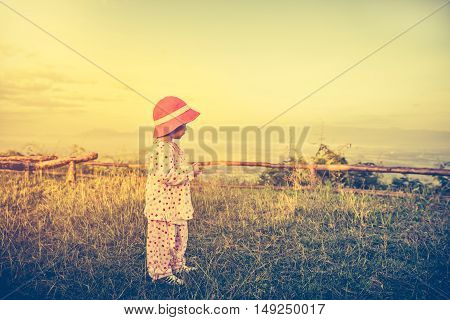 Asian Child Relaxing Outdoors, Travel On Vacation. Vintage Tone Effect.