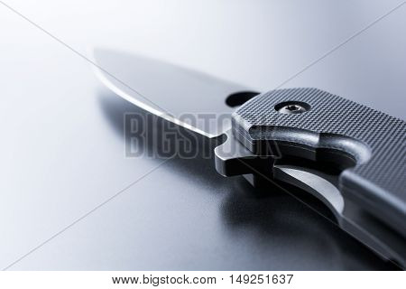 Closeup Of A Lying Opened Military Knife On Dark Ground