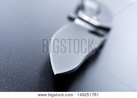 Macro Of A Knife Point Of An Opened Military Knife Which Is Lying On Dark Ground
