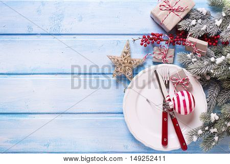 White plate knife and fork napkin and christmas decorations in white and red colors on blue wooden table. Top view. Selective focus. Place for text.