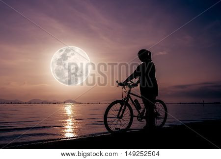 Silhouette of healthy biker-girl enjoying the view at seaside beautiful full moon on colorful sky background. Reflection of moon in water. Outdoors. The moon were NOT furnished by NASA.