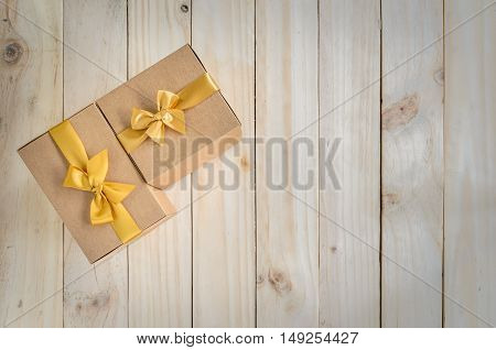 Brown gift boxes with gold bow on wooden background for copy space