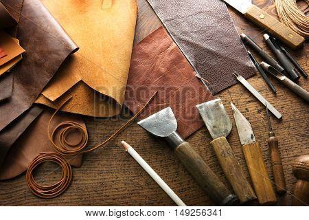 Leather craft or leather working. Leather working tools and cut out pieces of leather on leather craftman's work desk .