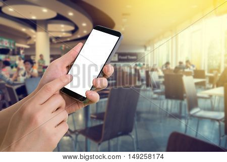 human hand hold and touch smartphone tablet cell phone with blank screen on blurred food court background.