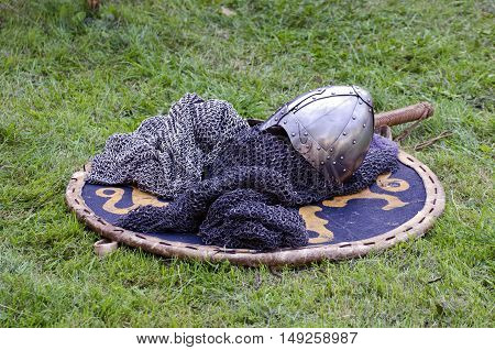Knight armor headpiece placed on shield on grass at medieval festival