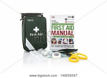 SWINDON UK - SEPTEMBER 25 2016: St John Ambulance First Aid Kit and Manual on a white background