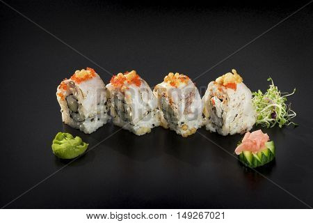 Uramaki maki sushi. Four rolls decorated with caviar and wasabi