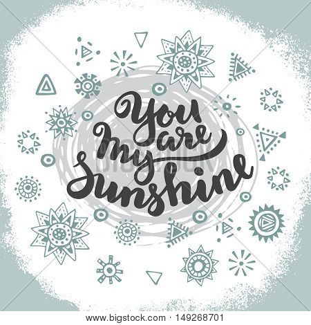 Handwritten quote You are my sunshine on hand drawn graphic ethnic background with doodle suns. Vector illustration for poster or card design.