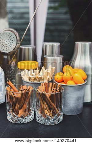 Making mulled wine for sale at country fair. Glintwine accesories, stirring wooden sticks, spices and citrus, cinnamon sticks and kumquat in glasses and metal bowls closeup. Vertical image