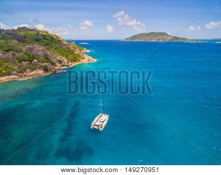 Aerial view of catamaran sailing in coastline. Tropical Seychelles island on background
