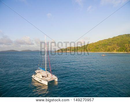 Aerial view of catamaran sailing in coastline. Tropical Seychelles island on background